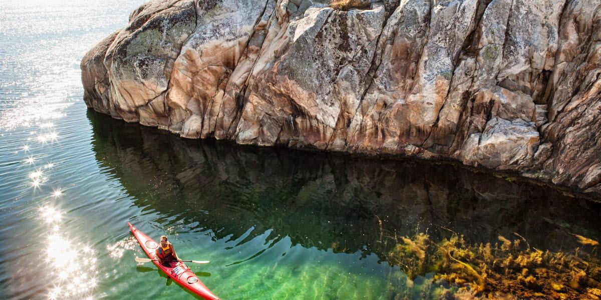 En röd kajak paddlar förbi en klippvägg. Det är en solig dag och vattnet är klart.