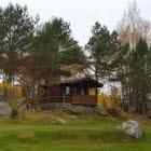 Vy över Camp Fjället utanför Tidaholm. Två bruna trästugor i skogskanten i höstskrud.