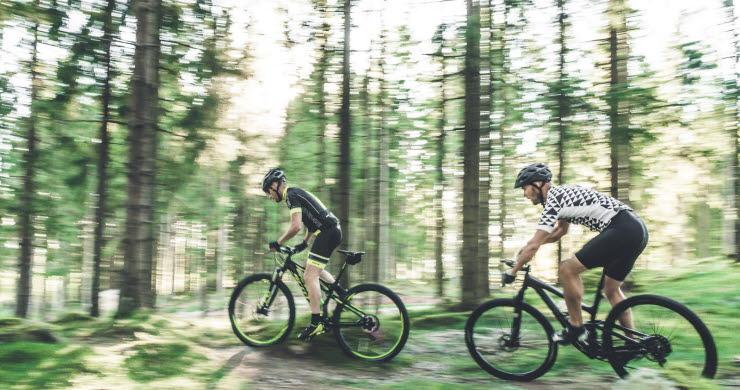 Två på rad kör mtb i skogen