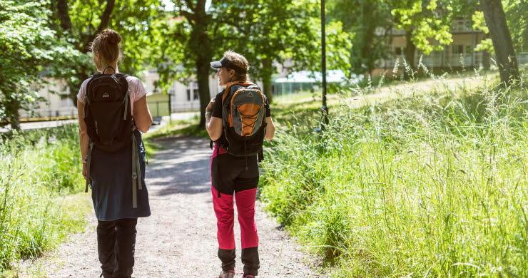 Två tjejer som vandrar med ryggsäckar.