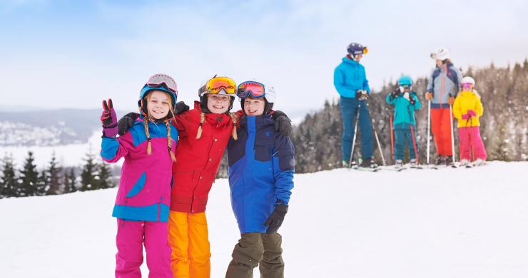 Tre barn i färgglada på toppen av Ulricehamn Ski Center.