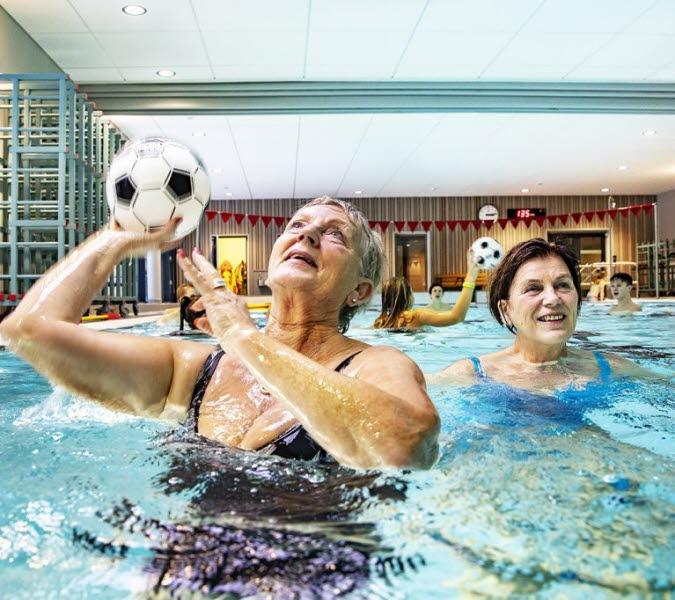 Två damer badar och kastar en boll mellan varandra