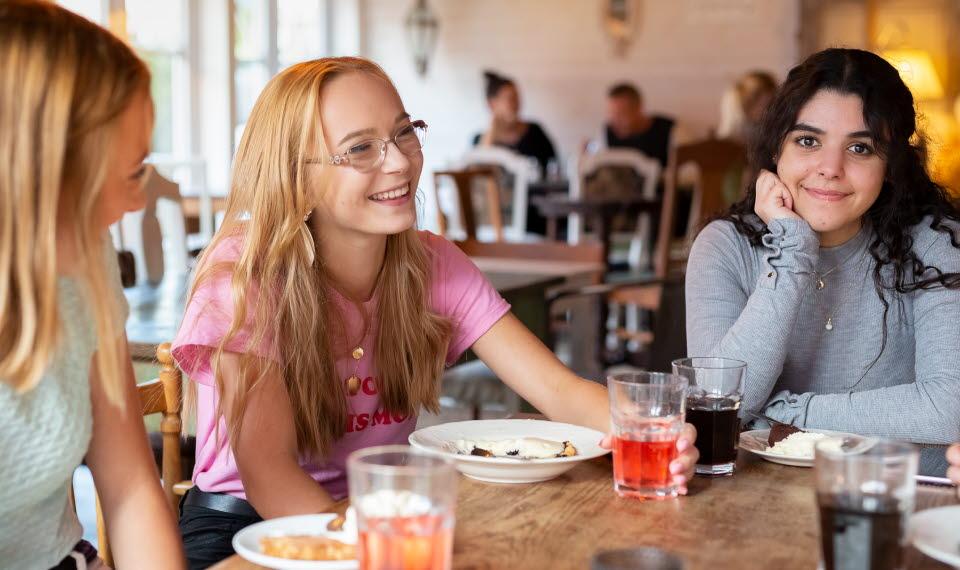 Tre tjejer fikar i Ulricehamn, en av de tittar rakt in i kameran.