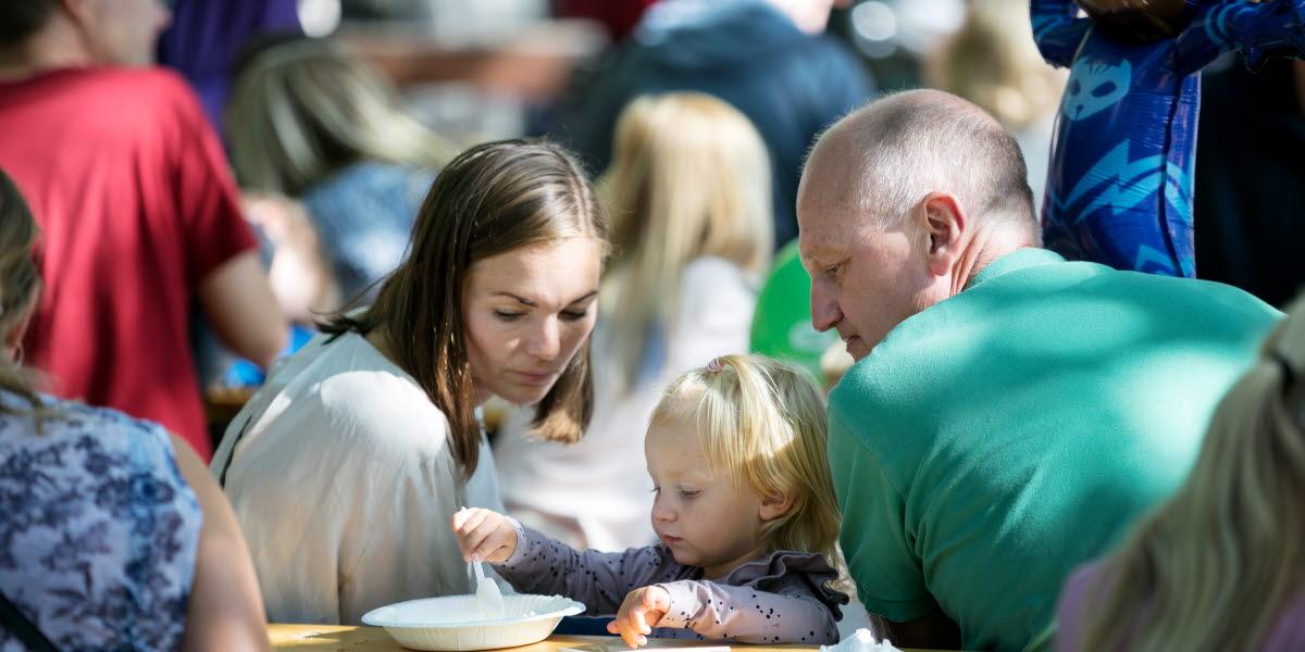 En kvinna och en man vakar över en liten flicka som sitter vid ett bord och äter själv.