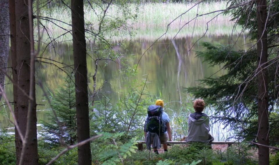 Två personer som tar rast vid en sjö i skogen.