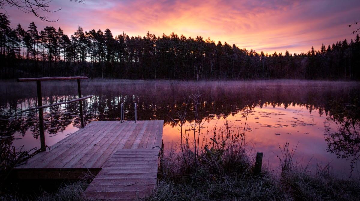 Solnedgång över en sjö med en frostig brygga. Färgerna på himlen skiftar i lila, rosa och orange