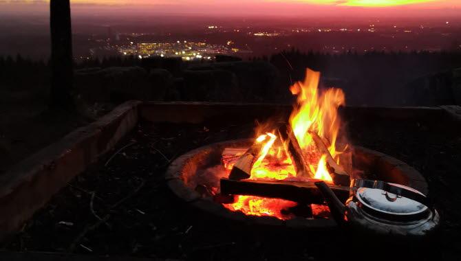 Sprakande eld framför en lika eldig och magnifik soluppgång med utsikt över staden.