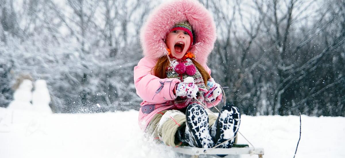 Flicka som åker pulka i snön.