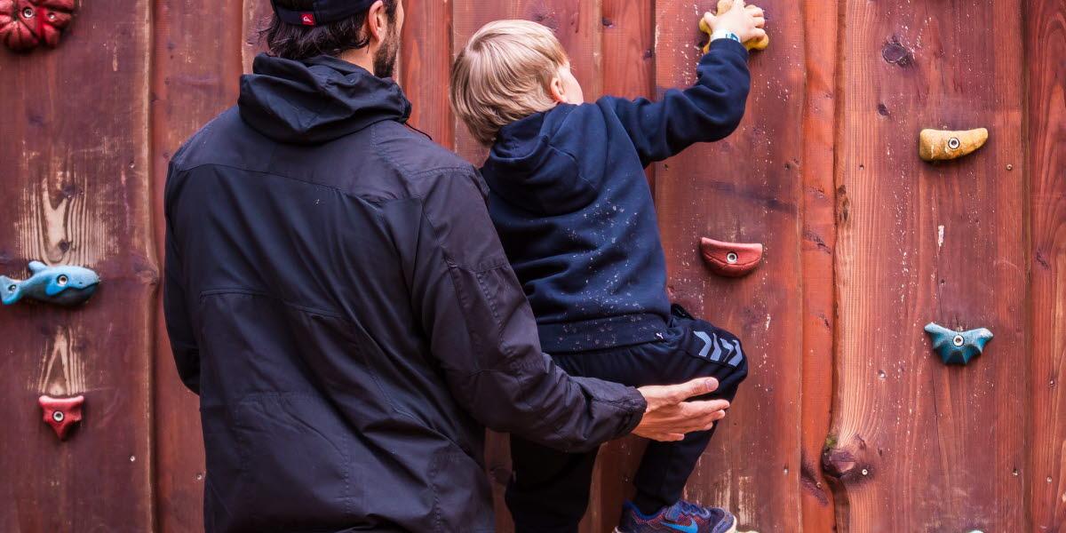 Ett litet barn klättrar på en klättervägg av trä. Barnets pappa stöttar barnet.