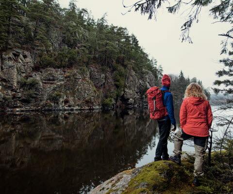 Två vandrare står nere vid vattnet och tittar på den branta bergsväggen på andra sidan sundet