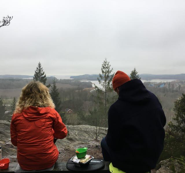 Två personer fikar på en utsiktsplats med utsikt över sjön Mjörn en lite grå men vacker vinterdag