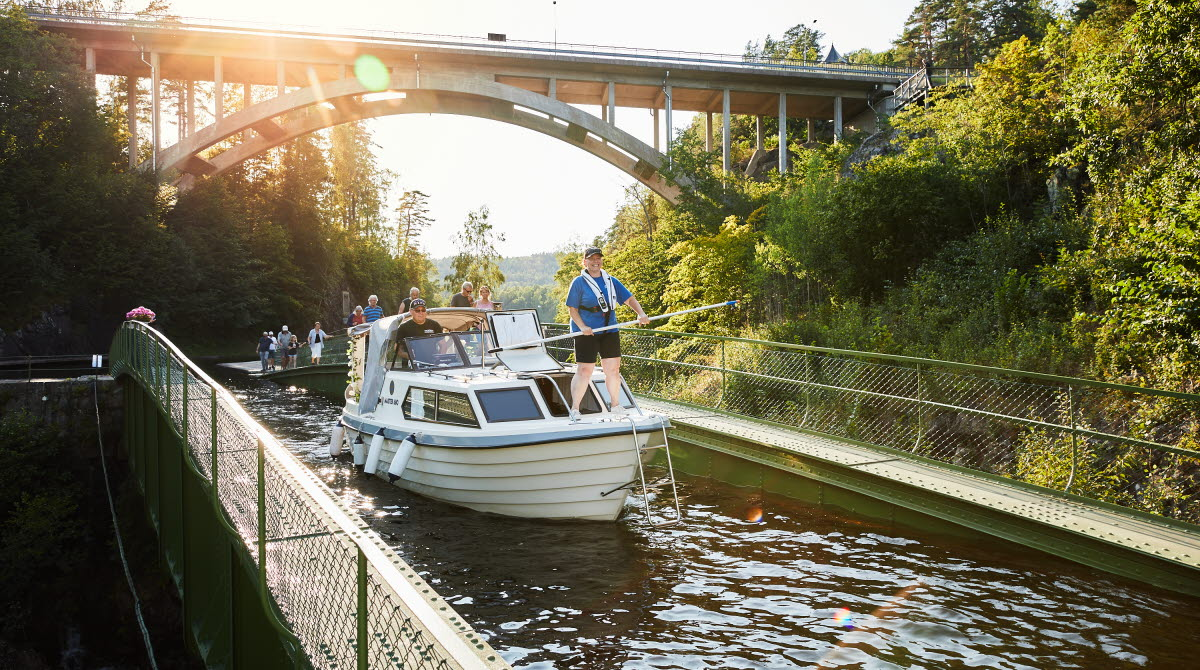 Glad kvinna i båt över akvedukten i Håverud.