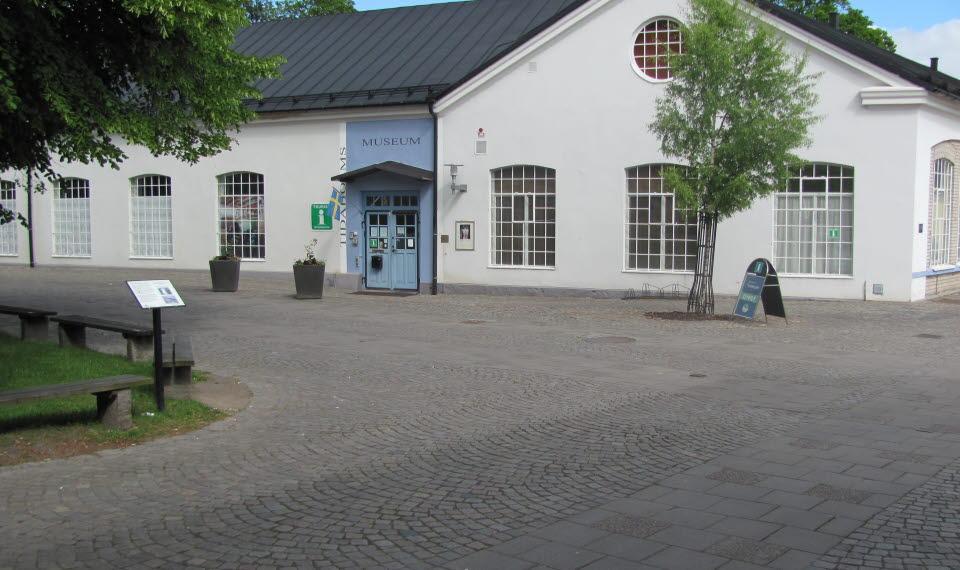 Tidaholms museums entré som är en vit stenbyggnad med en blå dörr i sommarskrud med en kullerstensgata framför.