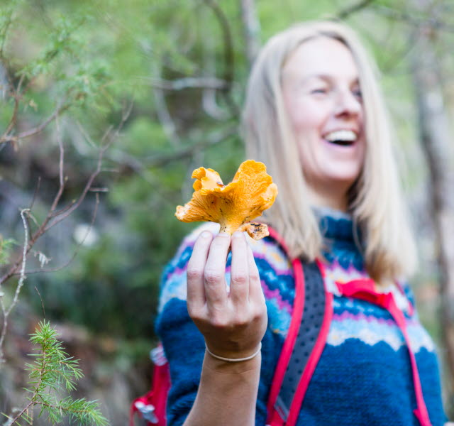 A happy woman is posing with a chanterelle in the woods.