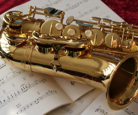 Saxofon som ligger på notblad med ett rött tyg under