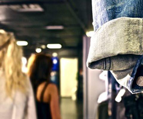 Två tjejer i klädbutik. Jeansjacka i förgrunden.