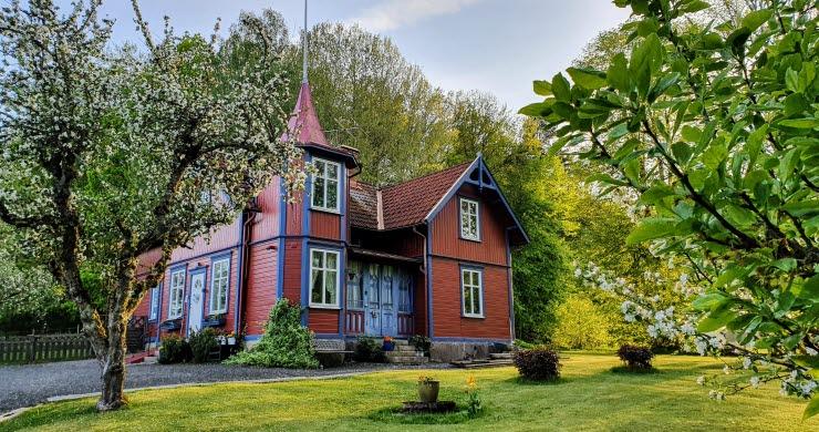 Vy över ett rött trähus med blåa knutar.