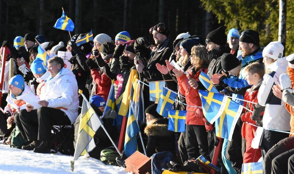 Publik utmed skidspåret som står och klappar händerna och viftar med svenska flaggan.