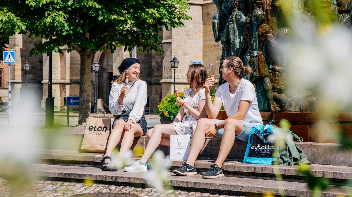 Tre personer sitter och samtalar vid Krönikebrunnen på Stortorget i Skara
