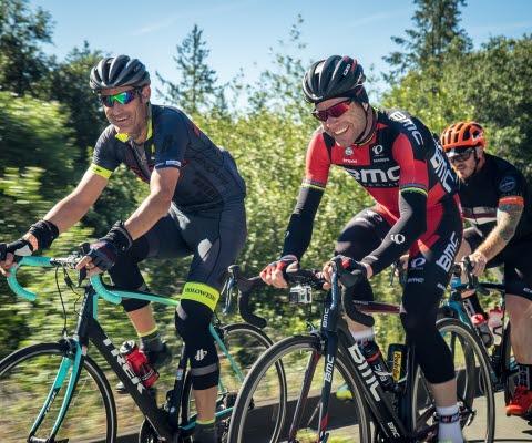 Tre män cyklar racercykel i härligt solsken