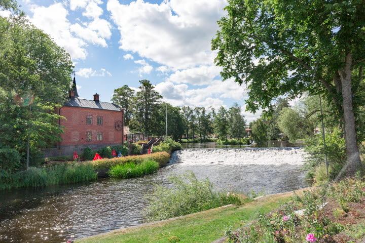 Vy över Turbinhuset på Turbinhusön i Tidaholm med ån Tidan rinnande framför.