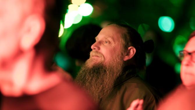 Man i stort och ståtligt skägg står i publikhavet och njuter av musiken på scen.