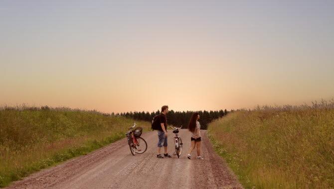 Man och kvinna som står på en grusväg med cyklar bredvid sig.