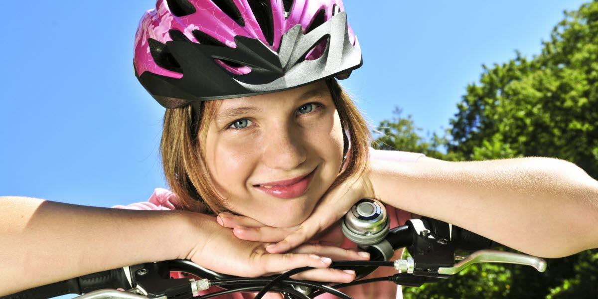 Glad flicka med cykelhjälm hänger över cykelstyret.