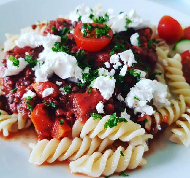 Mat på en vit tallrik. Snurrpasta med tomatsås, ost och persilja på