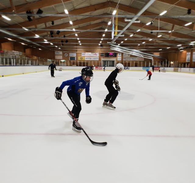Två killar åker skridskor i ishallen. Båda har hjälm och en av dem har en hockeyklubba.