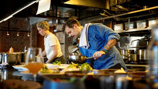 Två kockar står och lagar mat i en restaurang. Framför dem står tallrikar med mat på, färdiga att bli serverade.