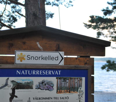 A wooden information board with a white, enameled sign with the text Snorkel-path on it, and a larger, blue enameled sign, welcoming you to Saltö nature reserve.