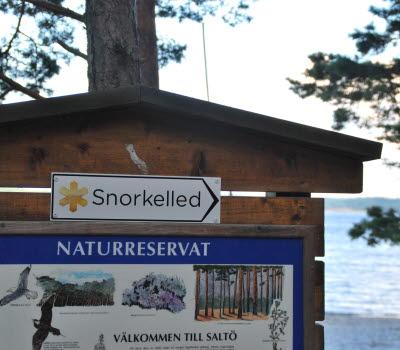 En informationstavla av trä där det sitter en vit emaljskylt som det står Snorkelled på, och en större, blå emaljskylt som välkommnar en till Saltö naturreservat.