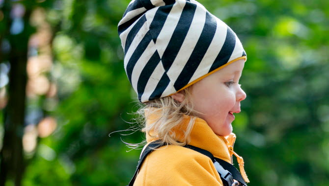Liten blond flicka är ute i naturen. På sig har hon en randig, svart och vit mössa samt en gul fleecejacka.