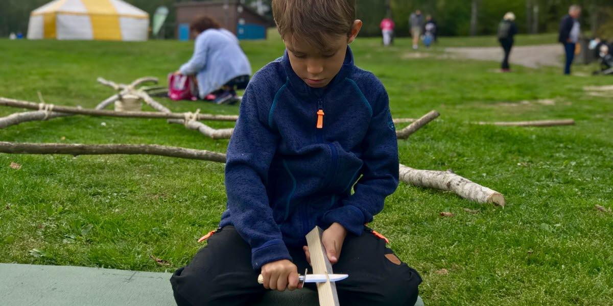 Liten pojke i blå fleecetröja sitter med en kniv i handen och täljer en träbit.