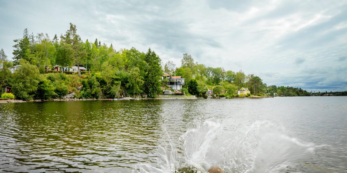 En person har hoppat i vattnet i Simsjön, och det skvätter vatten runt omkring. I bakgrunden syns en molntung himmel och en grön slänt med sommarstugor.