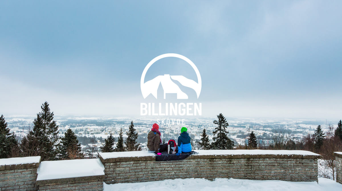 Två kvinnor sitter på muren vid utsiktsplatsen på Billingen och tittar ut över ett snötäckt Skövde.