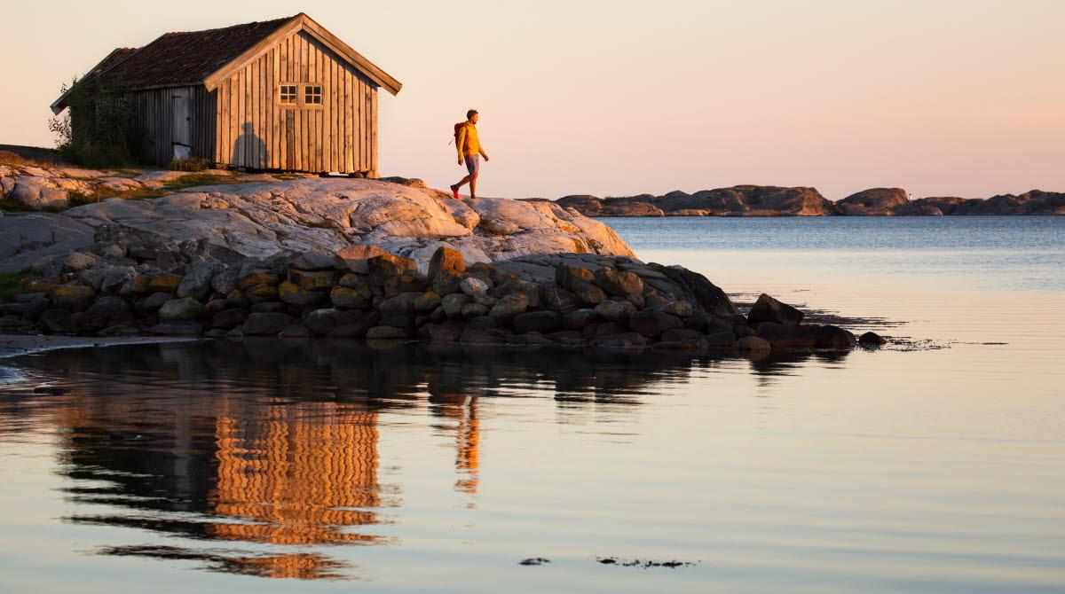 En person införd en gul tröja står på en klippa framför en gammal, grå sjöbod på Sydkoster. Havet ligger blankt och solen är på väg att gå ned.