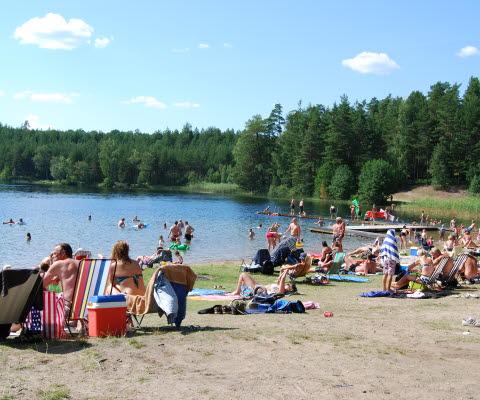 Lilla Havsjön som ligger på Hökensås naturområde. Folk som solar på stranden och folk som badar i sjön.