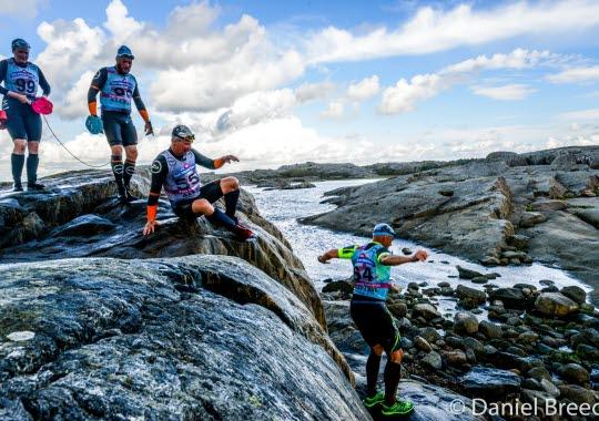 Fyra personer i våtdräkt springer över berget, de deltar i Swimrun på Öckerö