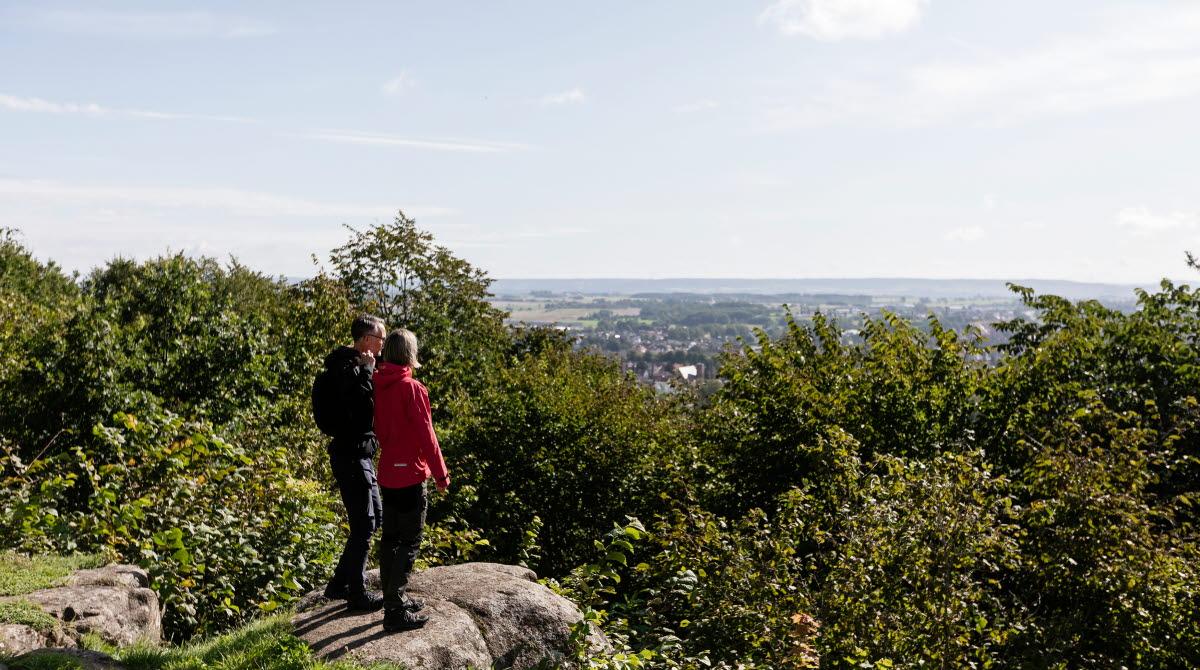 Kvinna och man som står på ett berg och kikar på utsikten över staden och landskapet.