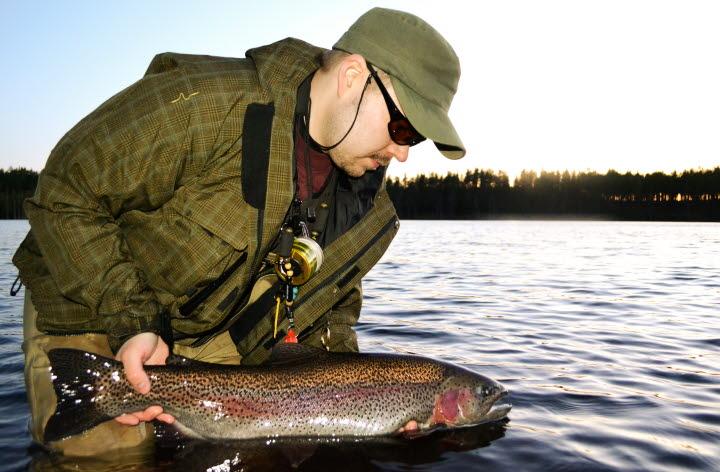 Man håller en fisk på Hökensås sportfiske.