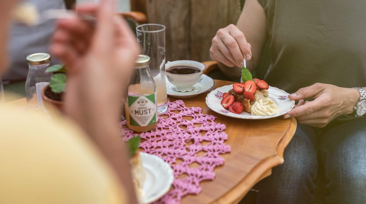 Fikabord med en kaka med jordgubbar och grädde.