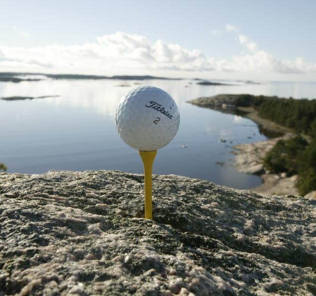 En golfboll placerad på en gul golfpeg, inkilad i ett berg. I bakgrunden syns Strömstads skärgård.