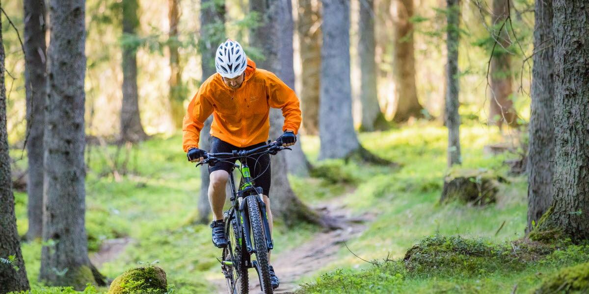 Man som cyklar mountainbike i skogen