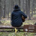 Person sitter på stock i skogen med gitarr i knät och väska bredvid sig.