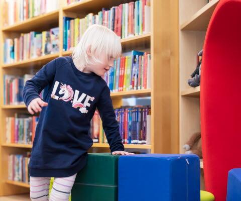 Ett barn försöker sätta sig till rätta bland sittpuffarna i biblioteket.