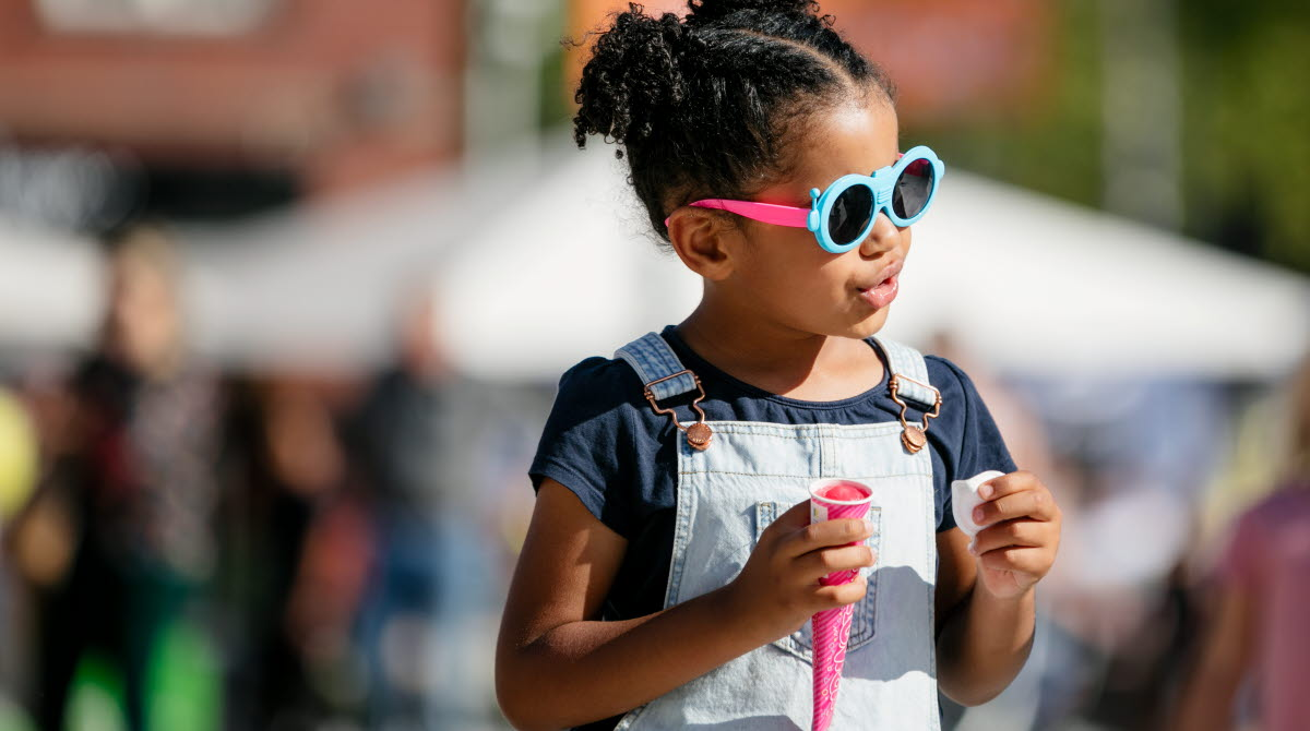 Liten flicka med svart krulligt hår iklädd snickarbyxor och coola solglasögon. I handen har hon en rosa glass.