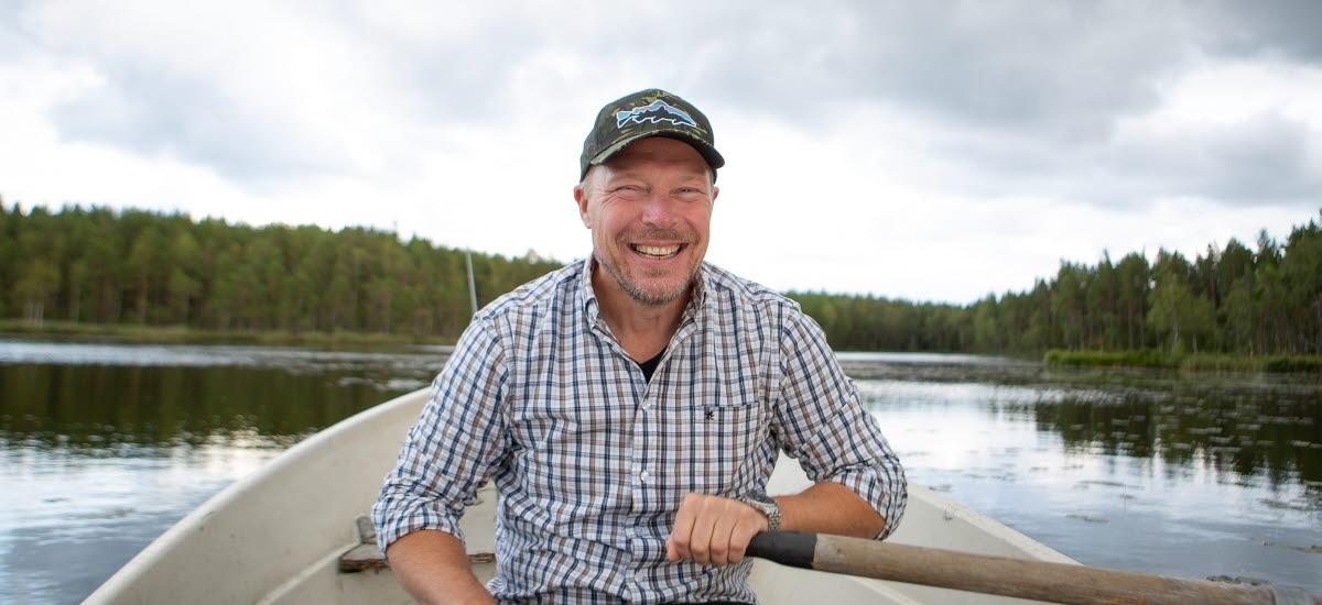 En man sitter i en eka och ror i en sjö.