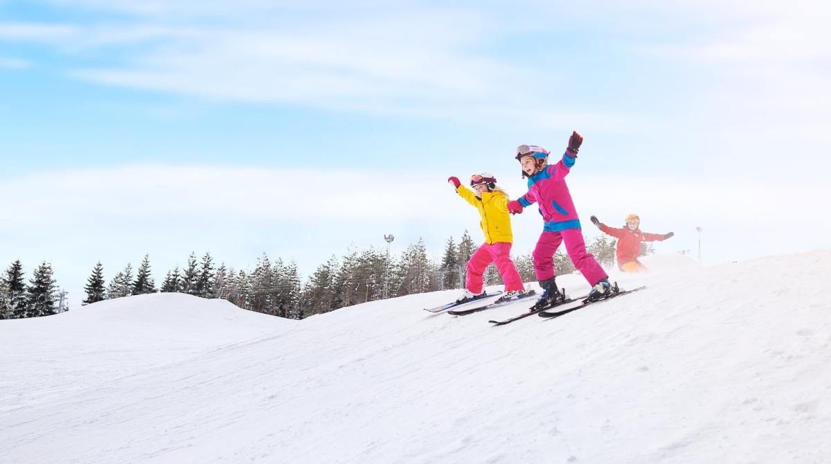 Två barn i färgglada kläder åker slalom på Ulricehamn Ski Center samtidigt som de håller varandra i handen.